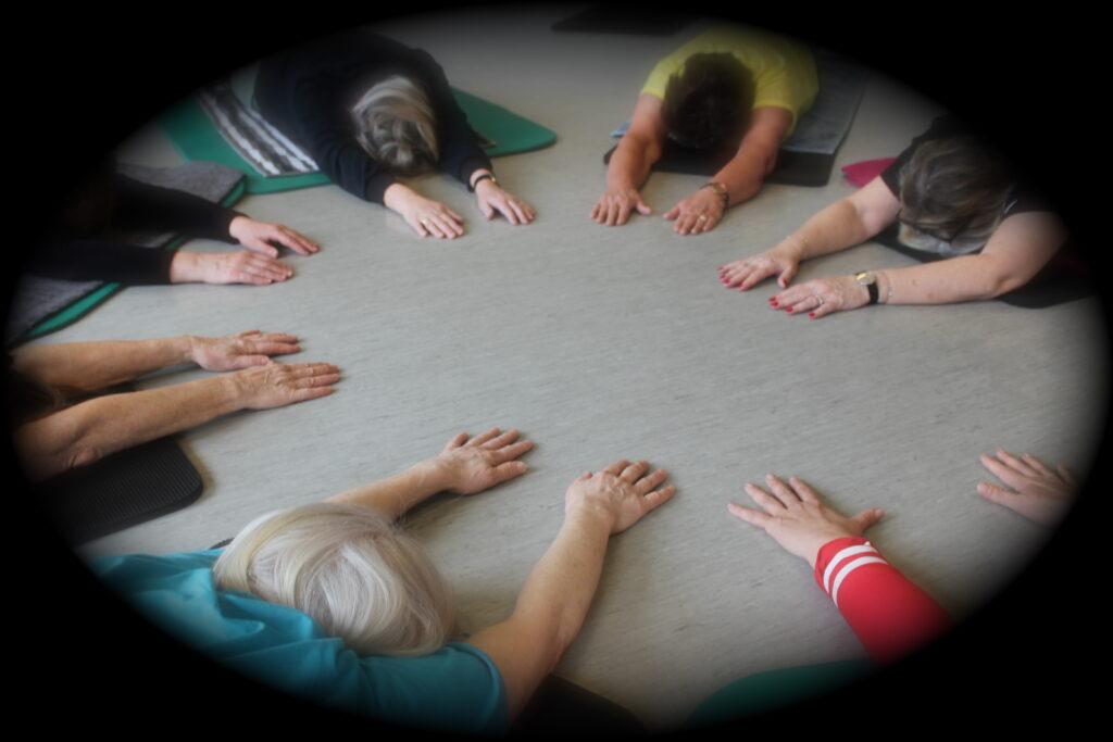 Udstrakte arme i cirkel på gulv viser mindfulness yoga.